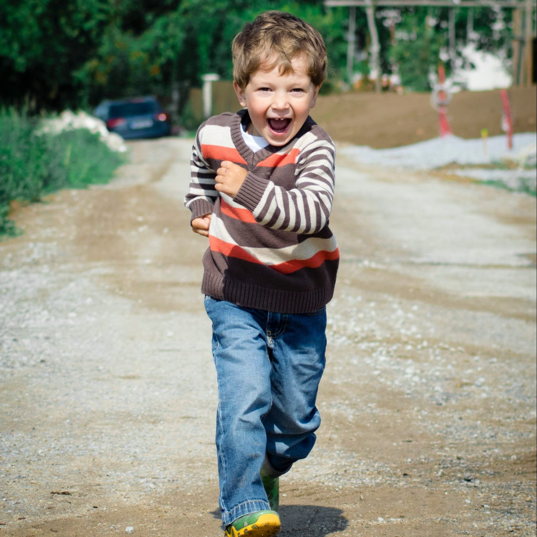 Young boy running happily towards the camera